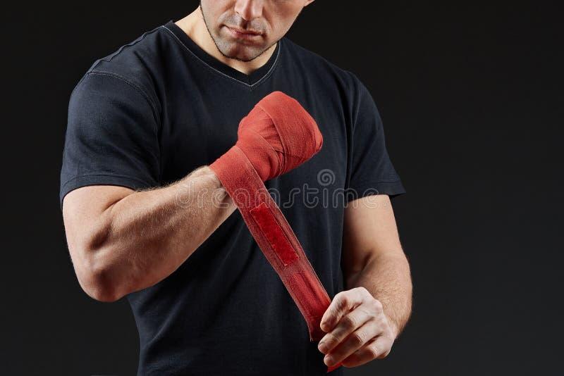 Zurückhaltendes Studioporträt des hübschen muskulösen Kämpfers, der für das Boxen auf Dunkelheit sich vorbereitet, verwischte Hin lizenzfreie stockfotos
