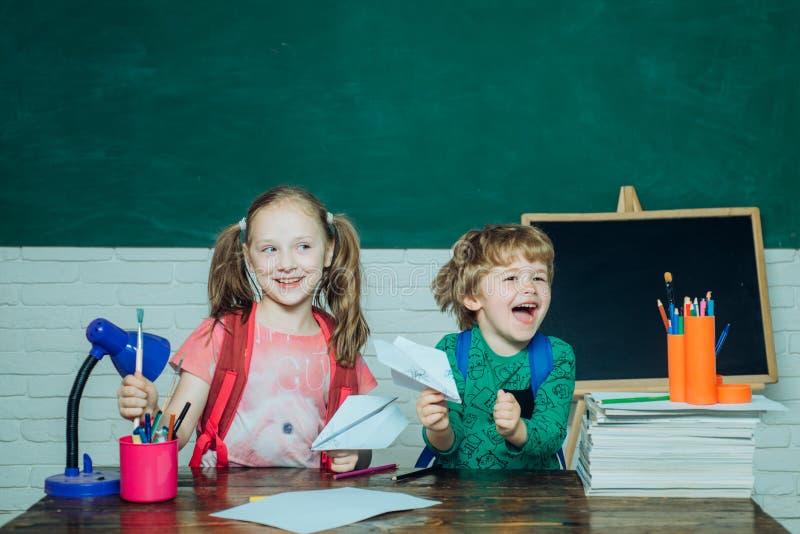 Zur?ck zu Schulbildungskonzept Wenig bereit zu studieren Mädchen und Junge mit glücklichem Gesichtsausdruck nahe Schreibtisch mit lizenzfreie stockfotografie