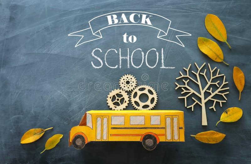 Zur?ck zu Schule Draufsichtfoto des Pappschulbusses mit hölzernen Gängen als Konzept des Erfolgs und Leistung nahe bei dem Herbst stockfotos
