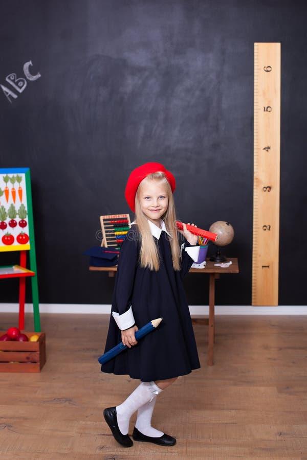 Zur?ck zu Schule! Ein kleines M?dchen steht mit gro?en Bleistiften in ihren H?nden in der Schule Schulm?dchen reagiert auf die Le stockfotografie