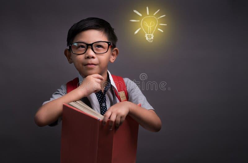 Zur?ck zu Schule, gl?ckliches Kinderkleinem Jungen mit dem Glasablesen B?cher, Konzept der Ausbildung und dem Ablesen stockfoto