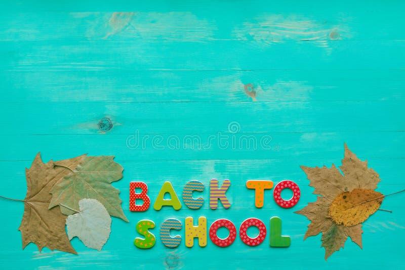 Zur?ck zu Schule-Konzept Draufsicht der bunten trockenen Blattfahne des Textes und des Herbstes über hölzernem Hintergrund mit Ko stockfotos