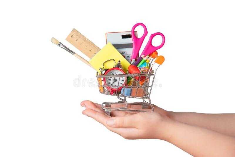 Zur?ck zu Schule-Konzept Helle Briefpapiereinzelteile in einer Minisupermarktlaufkatze in der Hand lokalisiert auf weißem Hinterg lizenzfreie stockbilder