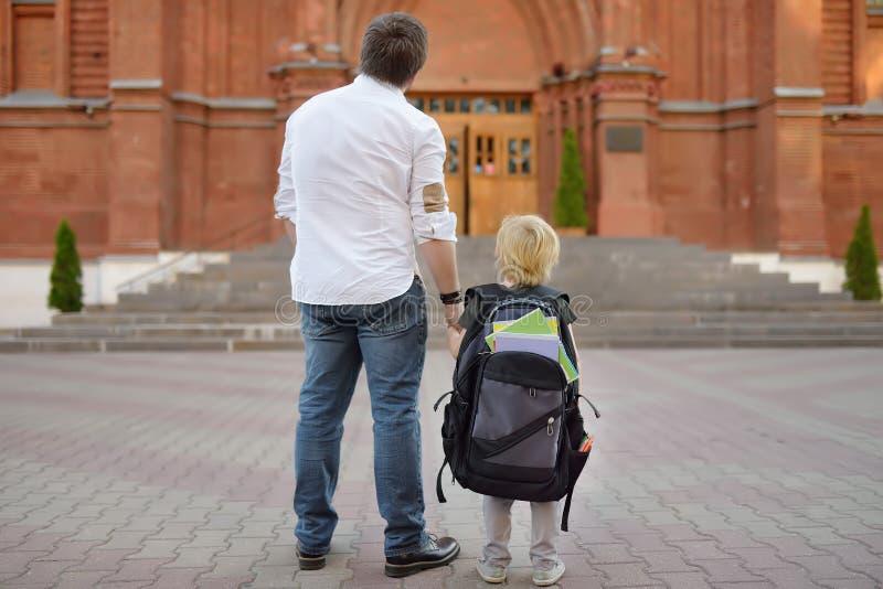Zur?ck zu Schule-Konzept Kleiner Sch?ler mit seinem Vater Erster Tag der Grundschule stockbild