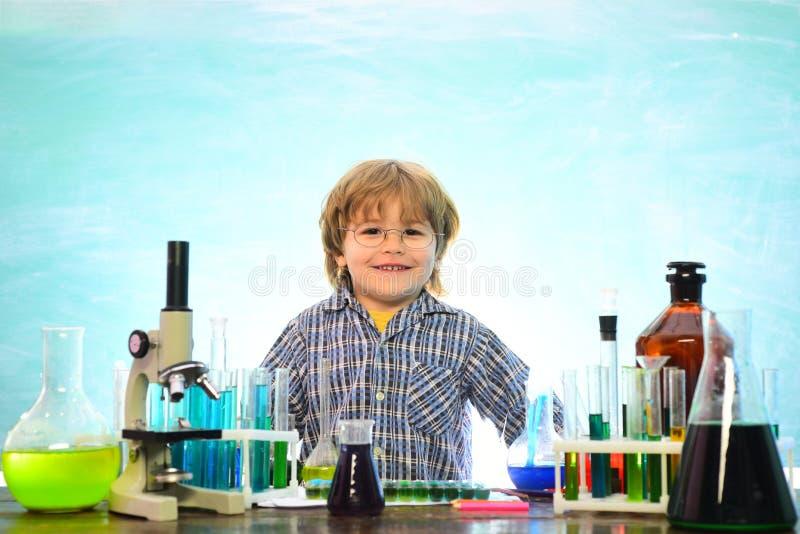 Zur?ck zu Schule und Hausunterricht Netter lächelnder kleiner Junge, der Spaß gegen blaue Wand hat Zur?ck zu Schule Erster Grad stockfoto