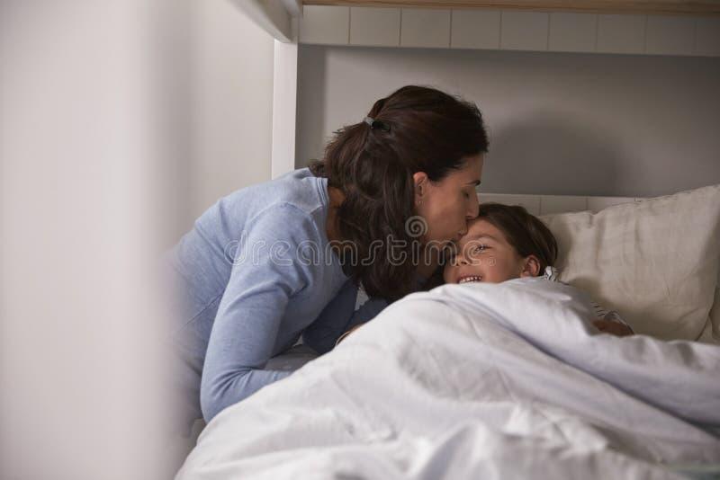 Zur Schlafenszeit küssende Mutter gute Nacht zur Tochter lizenzfreies stockbild