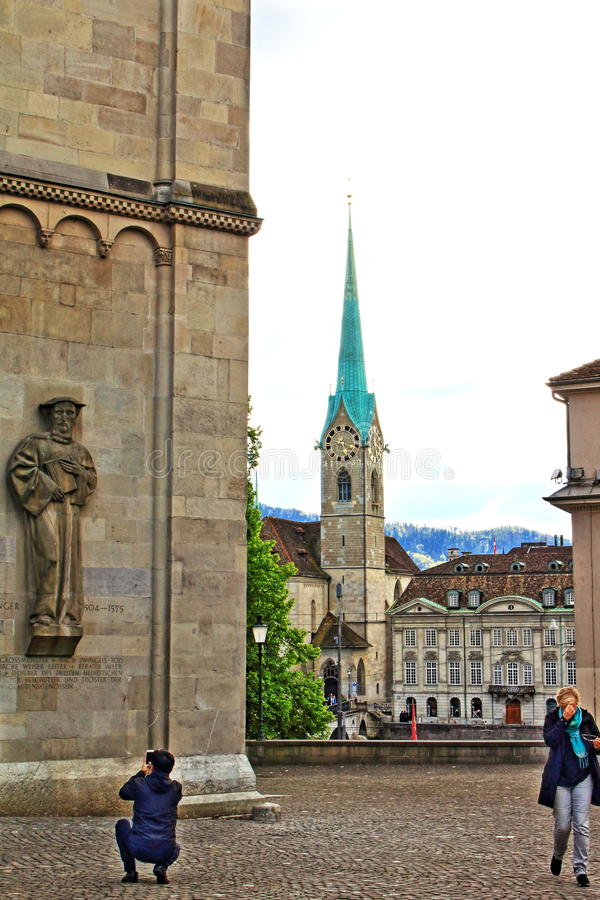 Zurich landmarks Switzerland. Statuary relief of Heinrich Bullinger on the southern exterior wall of the Grossmünster Cathedral and the tower of Fraumunster stock images