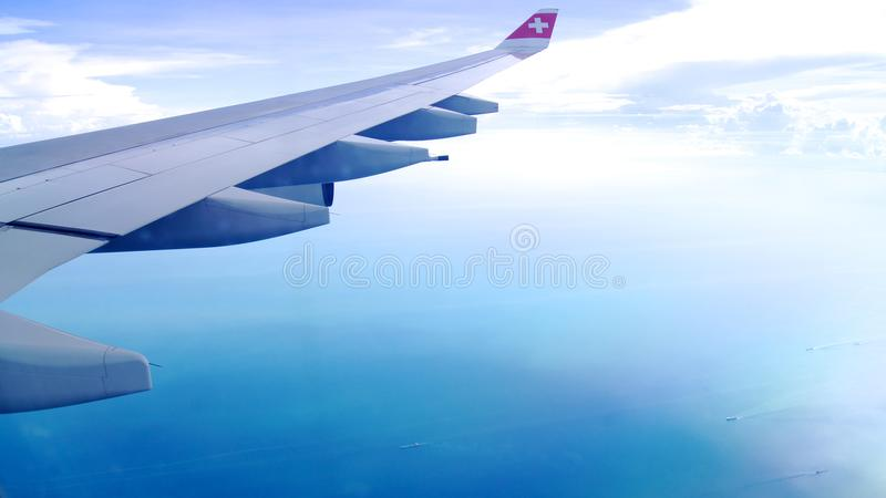 ZURICH, SWITZERLAND - MAR 31st, 2015: Wing View of an airplane during cloudy blue indigo sky royalty free stock photography