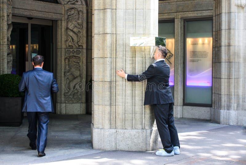 Zurique, Suíça - 5 de agosto de 2009 - um homem que beija uma coluna na entrada ao banco privado fotos de stock royalty free