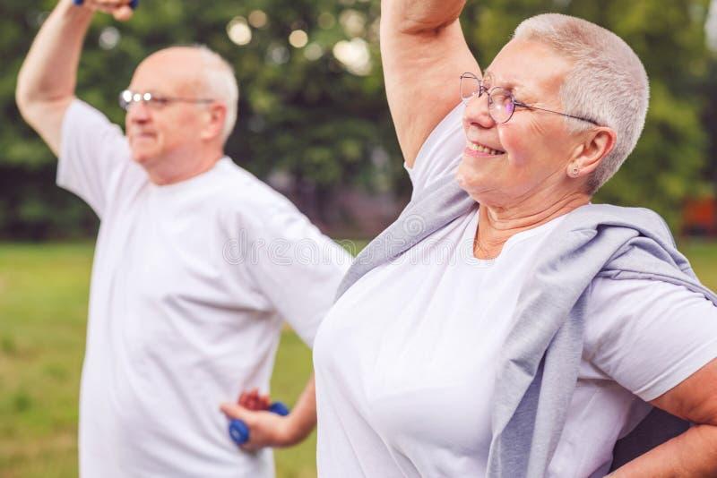Zusammen wir Training besser - glückliche ältere Paare trainieren und ha stockbild