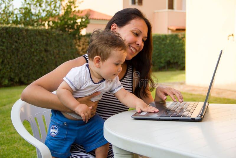 Zusammenarbeiten ist so die nette junge schöne Geschäftsfrau des Spaßes, die ihr Baby mit Lächeln beim Sitzen an ihrem Arbeiten b stockfotos