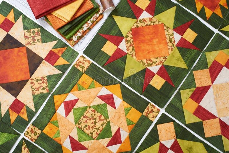 Zusammenbauen der Steppdecke von den orange-grünen Patchworkblöcken, Stapel des Gewebes lizenzfreie stockfotos