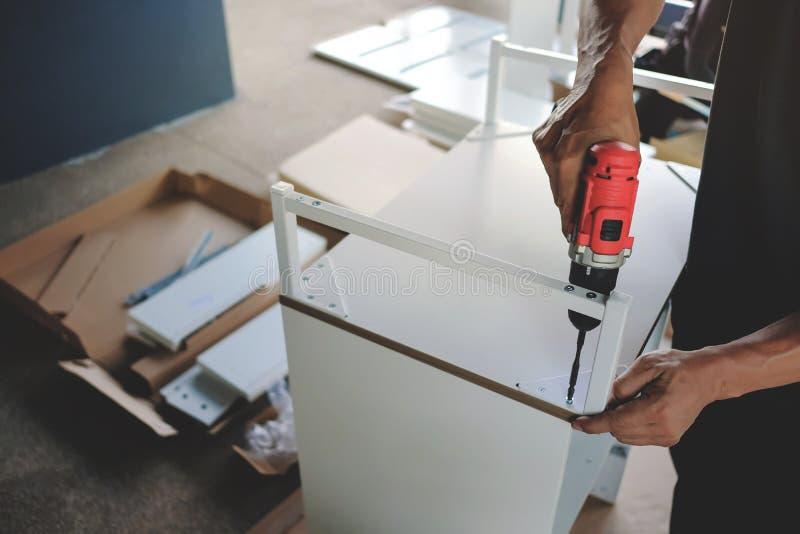 Zusammenbauende Möbel zu Hause Bewegen für ein neues Haus oder DIY-Konzept Handwerker, der drahtlosen Schraubenzieher verwendet stockfotos