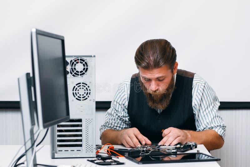 Zusammenbauender Computer des bärtigen Ingenieurs am Arbeitsplatz lizenzfreie stockfotografie