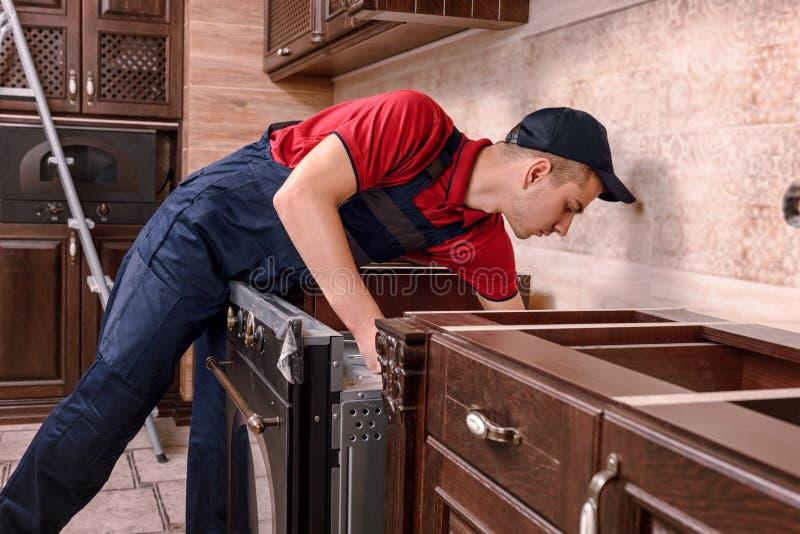 Zusammenbauender Ofen der Berufsarbeitskraft Installation von Küchenmöbeln stockfoto