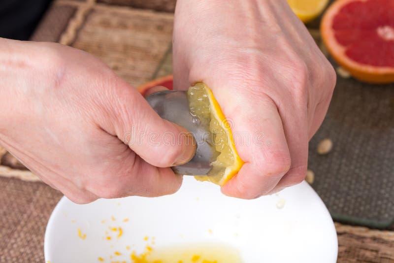Zusammendrücken der Zitrone mit Metalllöffel lizenzfreie stockbilder