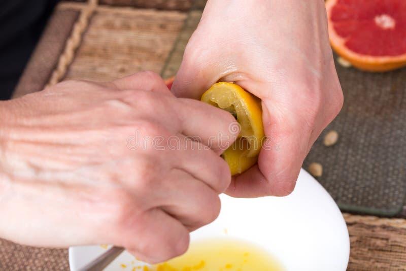 Zusammendrücken der Zitrone mit Metalllöffel stockbilder