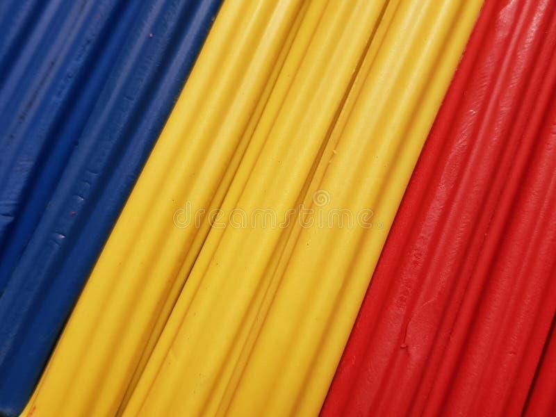 Zusammenfassung mit Plasticinestangen in der blauen, gelben und roten Farbe, im Hintergrund und in der Beschaffenheit lizenzfreie stockfotos