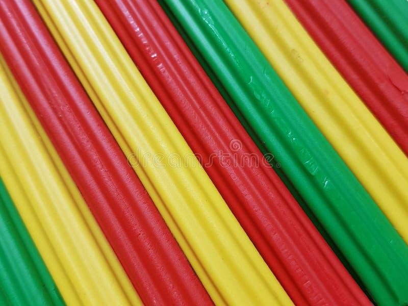 Zusammenfassung mit Plasticinestangen in der grünen, gelben und roten Farbe, im Hintergrund und in der Beschaffenheit stockfoto