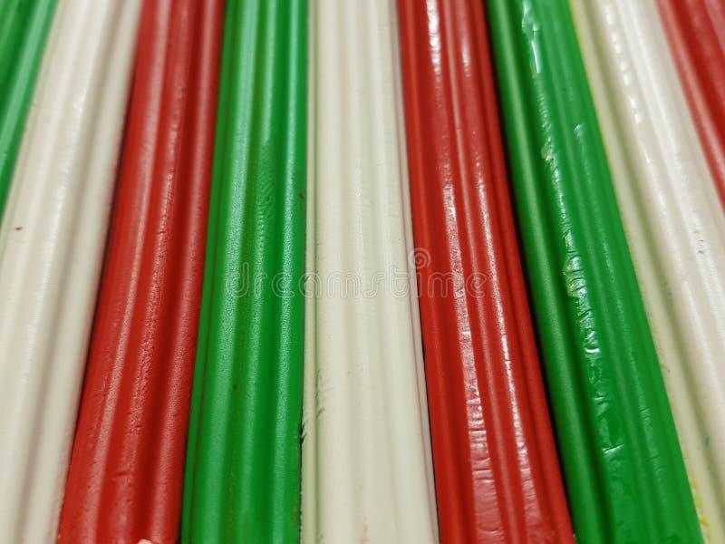 Zusammenfassung mit Plasticinestangen in der grünen, weißen und roten Farbe, im Hintergrund und in der Beschaffenheit lizenzfreie stockbilder