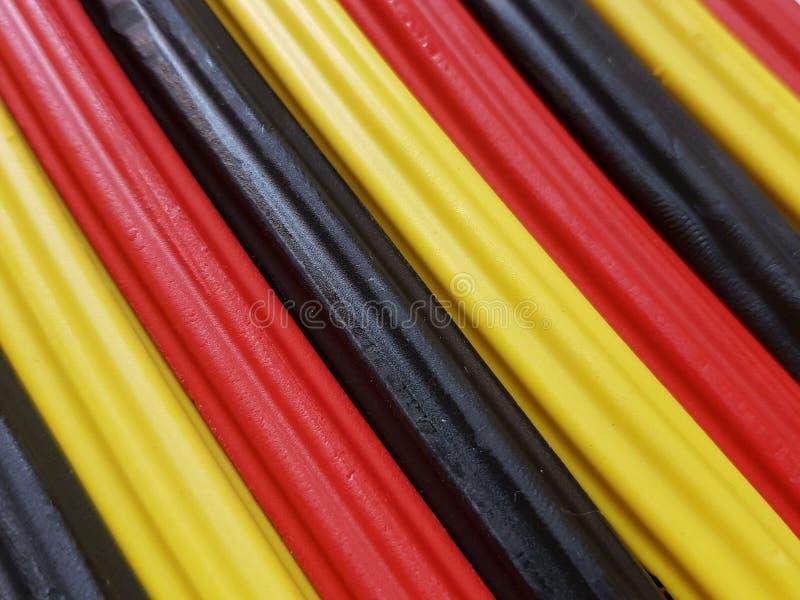 Zusammenfassung mit Plasticinestangen in der schwarzen, gelben und roten Farbe, im Hintergrund und in der Beschaffenheit stockbilder