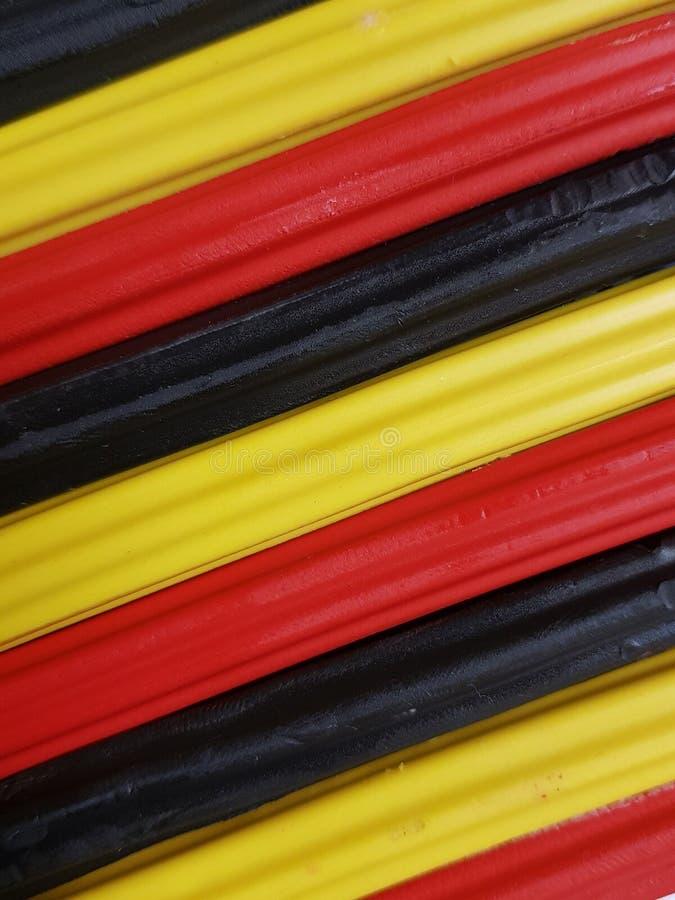 Zusammenfassung mit Plasticinestangen in der schwarzen, gelben und roten Farbe, im Hintergrund und in der Beschaffenheit lizenzfreies stockfoto