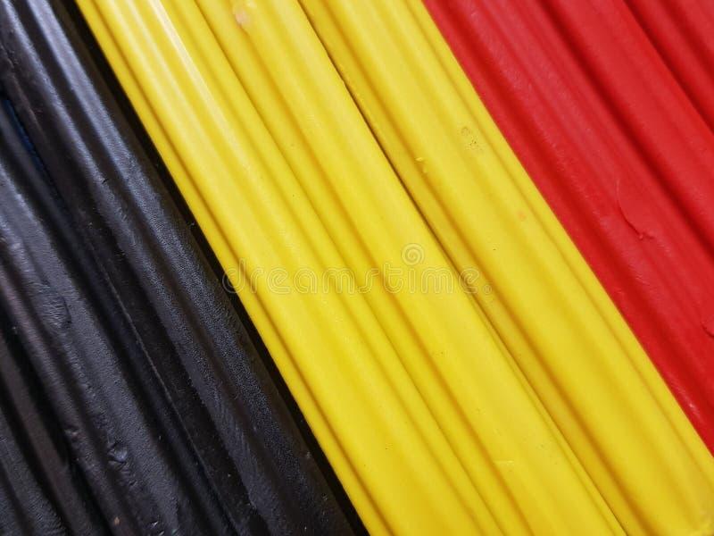Zusammenfassung mit Plasticinestangen in der schwarzen, gelben und roten Farbe, im Hintergrund und in der Beschaffenheit lizenzfreie stockbilder