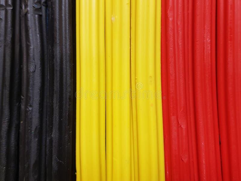 Zusammenfassung mit Plasticinestangen in der schwarzen, gelben und roten Farbe, im Hintergrund und in der Beschaffenheit stockfotos