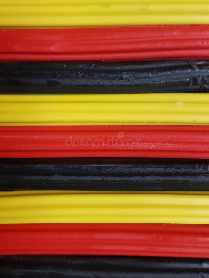 Zusammenfassung mit Plasticinestangen in der schwarzen, gelben und roten Farbe, im Hintergrund und in der Beschaffenheit lizenzfreies stockbild