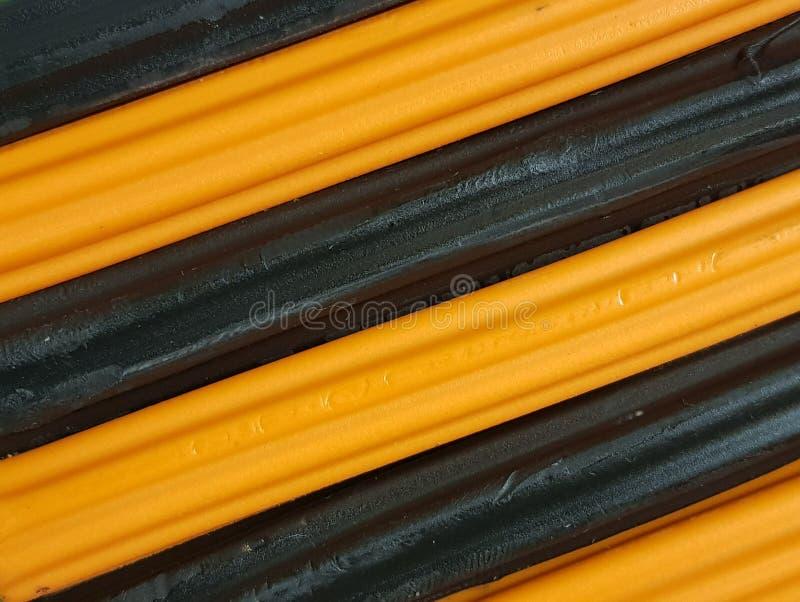 Zusammenfassung mit Plasticinestangen in der schwarzen und orange Farbe, im Hintergrund und in der Beschaffenheit lizenzfreies stockfoto