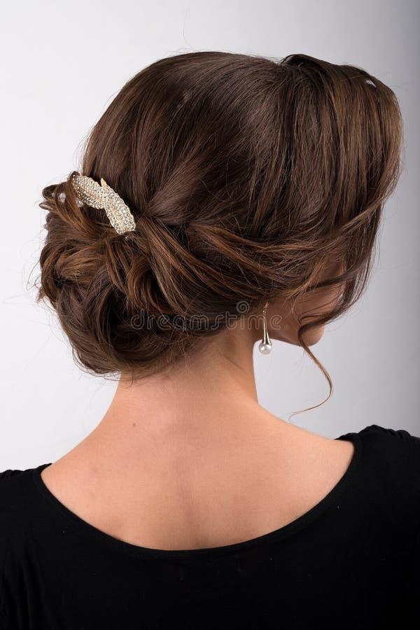 Zusammengebautes dunkles Haar der formalen Frisur verziert mit dem Kamm in Form von Blättern, Seitenansicht stockfotografie