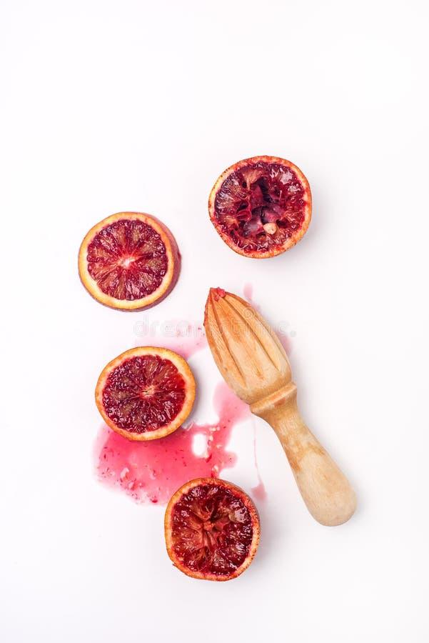 Zusammengedrückte geschnittene reife saftige sizilianische Blutorangen auf weiße Hintergrund-geschmackvolle Orangen-hölzerne Quet stockfoto