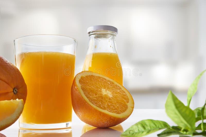 Zusammengedrückter Orangensaft im Glas auf weiße Küche horizontalem Compo lizenzfreie stockfotos