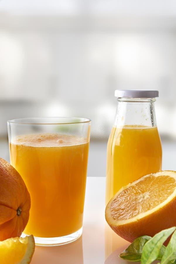 Zusammengedrückter Orangensaft im Glas auf weißem Küchenvertikale composi lizenzfreie stockfotografie