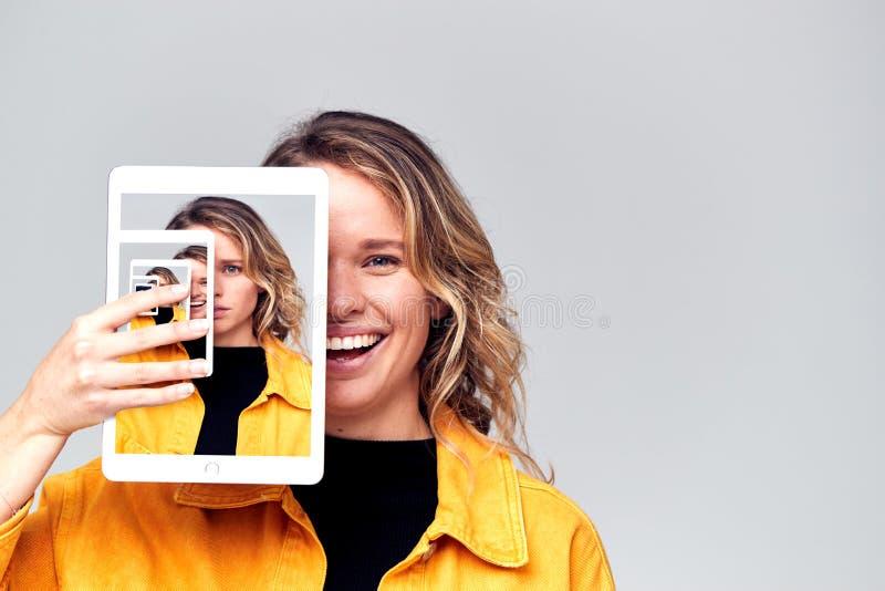 Zusammengefasstes Concept Image, das widersprüchliche Emotionen von Frauen zeigt und soziale Medien mit digitalen Tablet-PCs nutz lizenzfreie stockfotografie