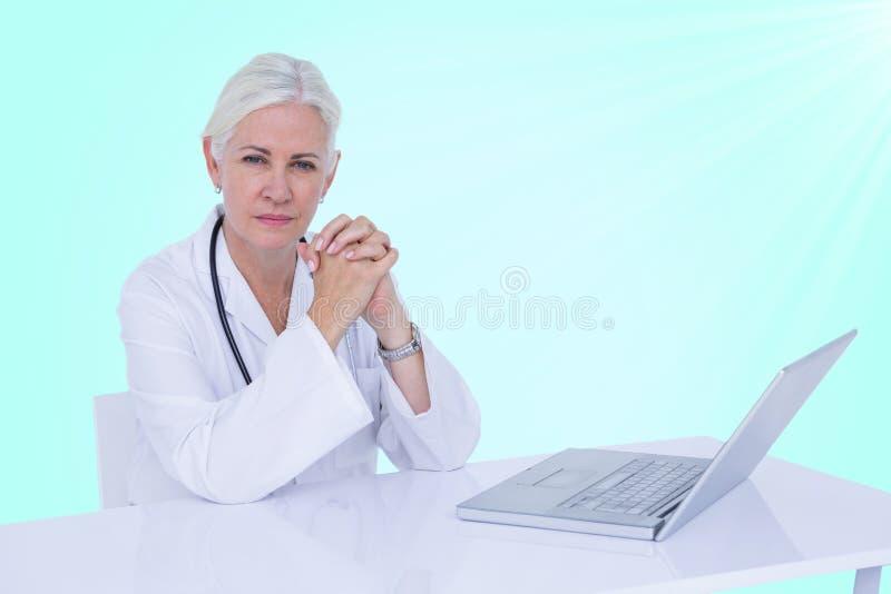Zusammengesetztes Bild 3d des Porträts der überzeugten Ärztin mit Laptop auf Schreibtisch stockfotografie