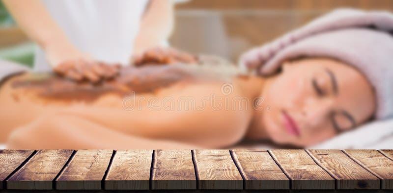Zusammengesetztes Bild der attraktiven Frau hintere Maske der Schokolade in der Badekurortmitte empfangend stockbild