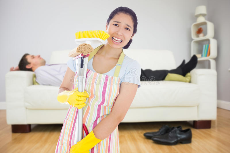 Zusammengesetztes Bild der beunruhigten Frau, die Reinigungswerkzeuge hält stockbilder