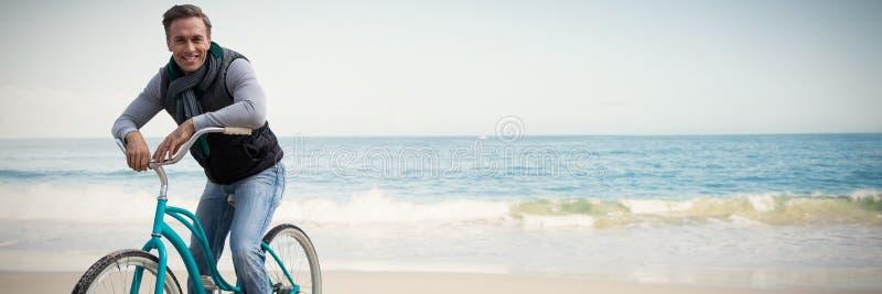 Zusammengesetztes Bild der digitalen Zusammensetzung des gutaussehenden Mannes auf einer Fahrradfahrt lizenzfreie stockfotografie