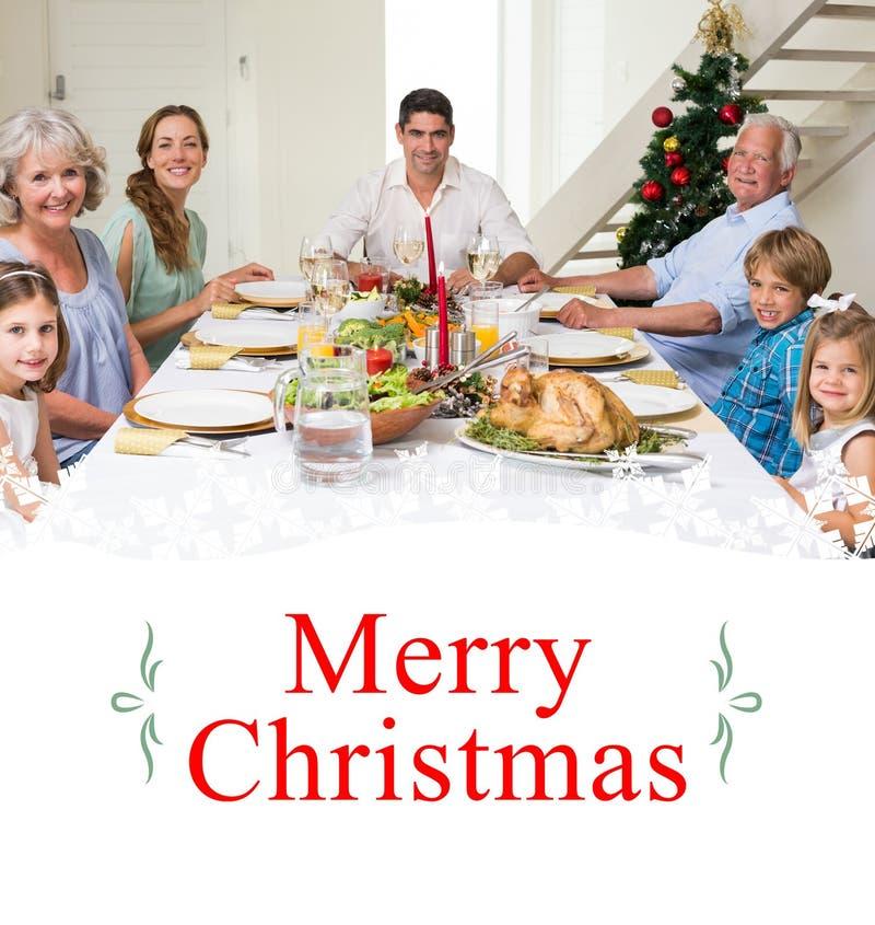 Zusammengesetztes Bild der Familie, die Weihnachtsmahlzeit zusammen hat lizenzfreies stockbild
