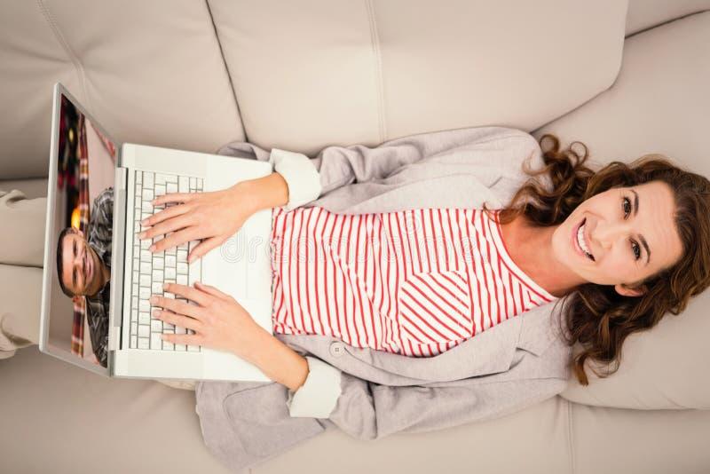 Zusammengesetztes Bild der Frau, die Laptop beim auf Sofa zu Hause liegen verwendet lizenzfreie stockfotos