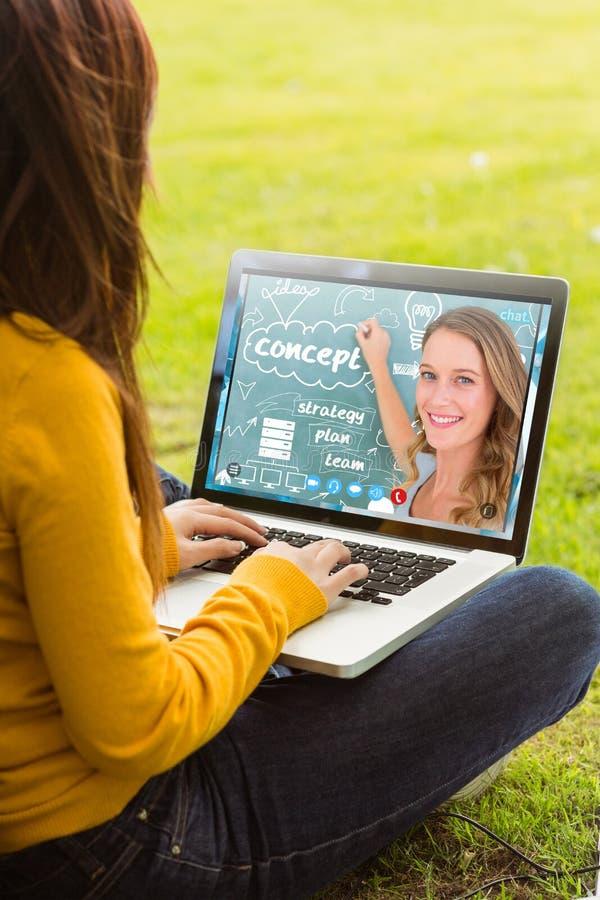 Zusammengesetztes Bild der Frau, die Laptop im Park verwendet lizenzfreies stockbild