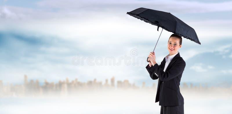 Zusammengesetztes Bild der Geschäftsfrau einen schwarzen Regenschirm halten stockfotografie