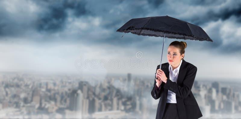 Zusammengesetztes Bild der Geschäftsfrau einen schwarzen Regenschirm halten lizenzfreie stockfotos