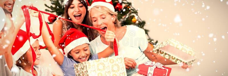 Zusammengesetztes Bild der glücklichen Familie an den Weihnachtsöffnungsgeschenken zusammen lizenzfreie stockfotografie