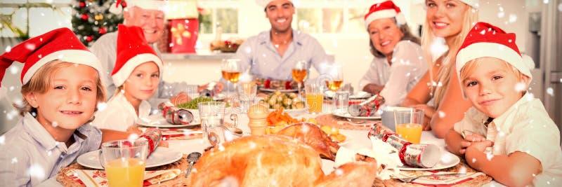 Zusammengesetztes Bild der glücklichen Familie Sankt-Hüte um den Abendtisch tragend lizenzfreie stockfotos