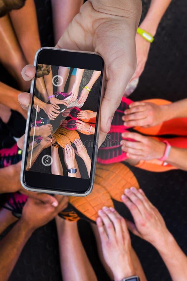 Zusammengesetztes Bild der Hand Handy gegen weißen Hintergrund halten stockbilder