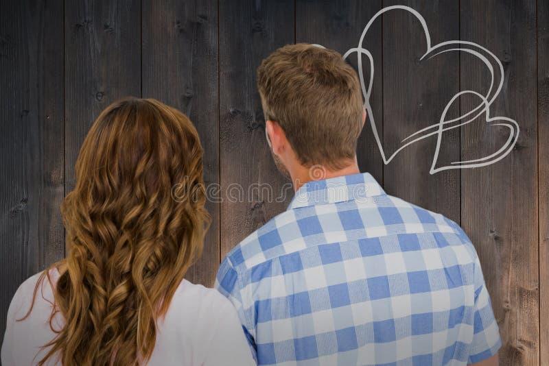 Zusammengesetztes Bild der hinteren Ansicht der jungen Paarstellung lizenzfreie stockbilder