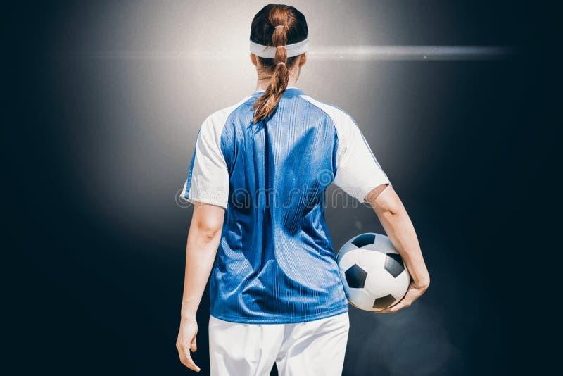 Zusammengesetztes Bild der hinteren Ansicht des Frauenfußballspielers, der einen Ball hält lizenzfreies stockbild