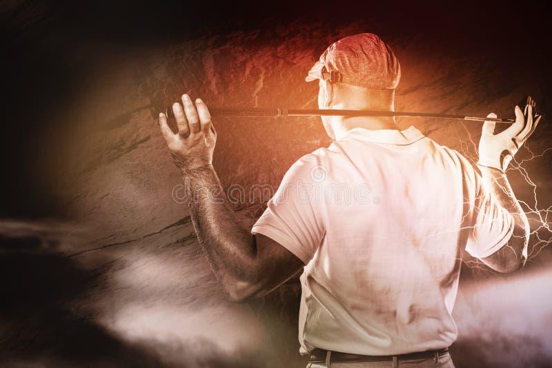 Zusammengesetztes Bild der hinteren Ansicht des Golfspielers einen Golfclub halten lizenzfreies stockbild